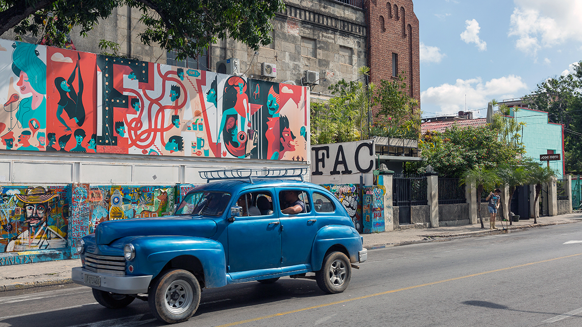 Vintage american car from 40s cruising the streets of Havana, in the background Fabrica de Arte Cubano