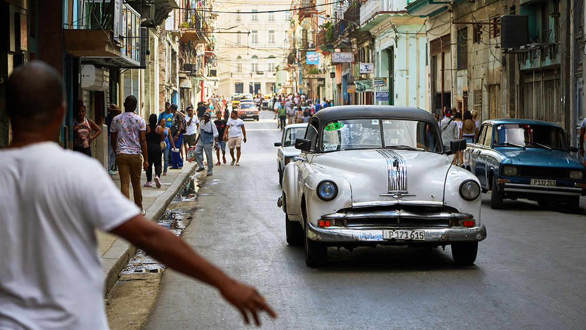Habanero in Havana Centro making signs to stop an 'almendron', a taxi in a vintage american car, Joanna Lumley's documentary film