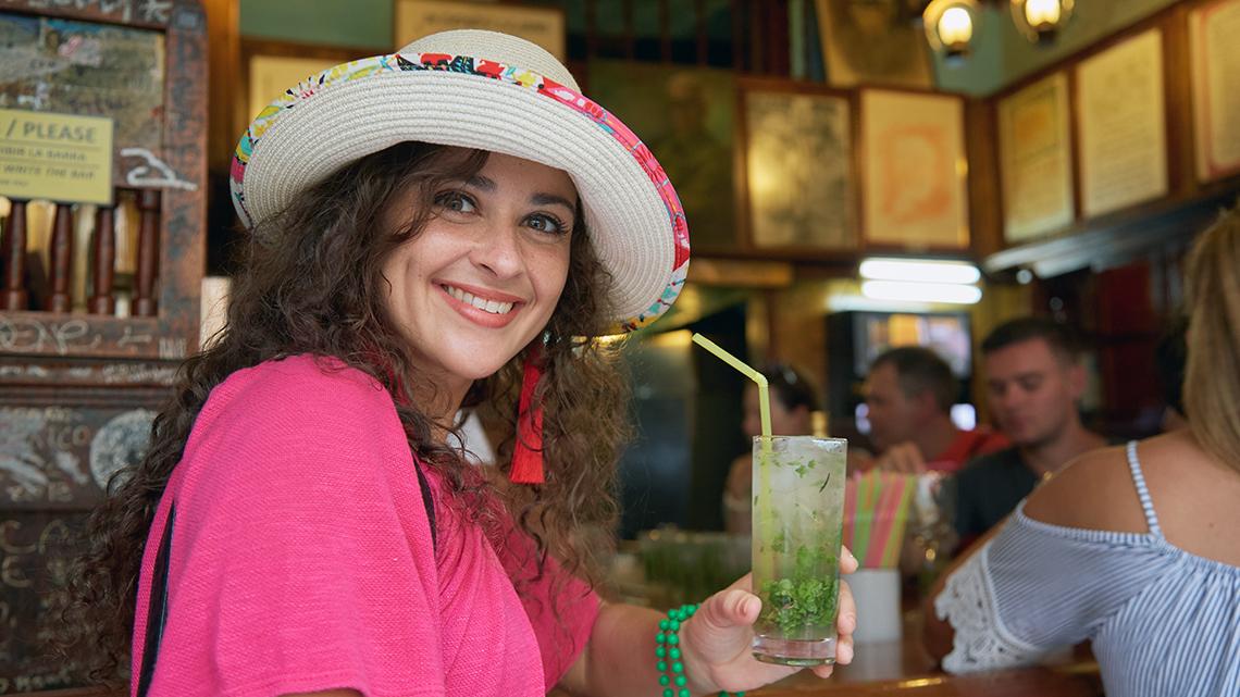 Tourist drinking a classic Mojito in La Bodeguita del Medio in Old Havana, Cuba