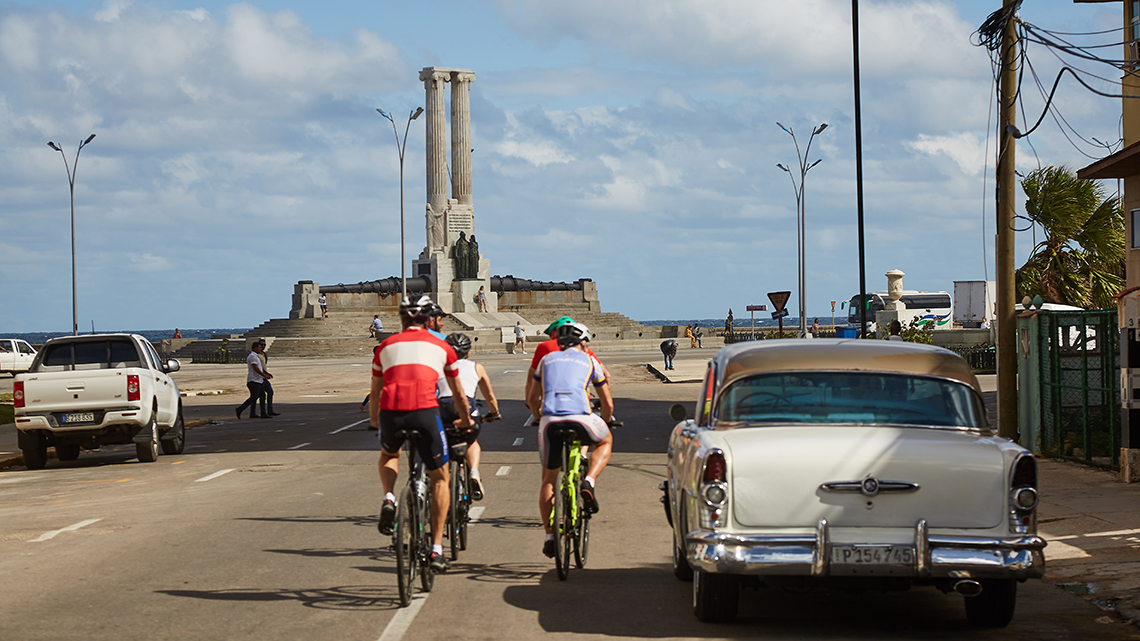 A small group of cyclists riding with Cubania Travel towards Havana's Malecon