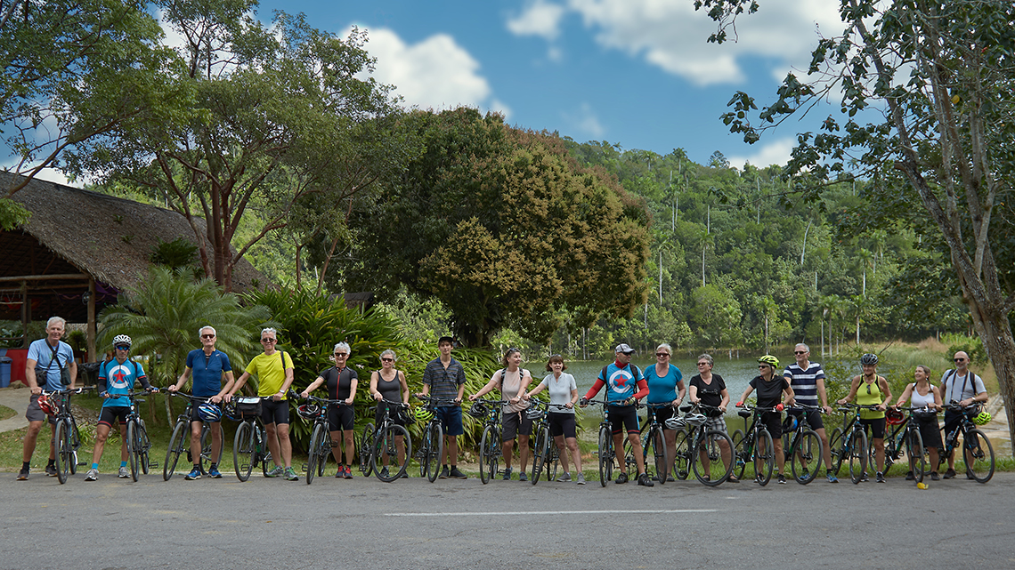 Group of cyclist pose with their Cubania Travel guides in Las Terrazas