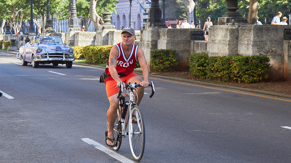Young Cuban hipster biking along Paseo del Prado in Old Havana