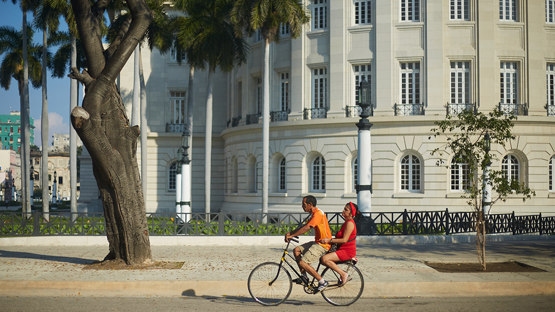 Couple ride in an old Minerva bike in Old Havana, in the background El Capitolio