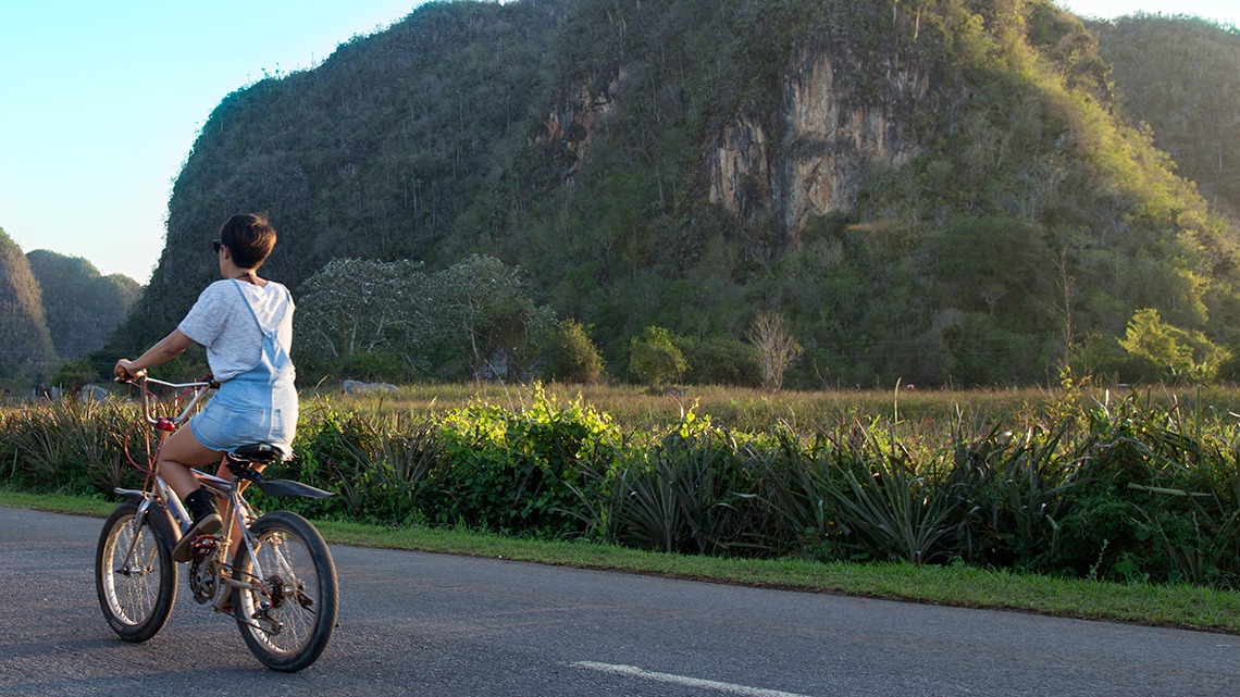 Young Cuban lady riding her bike along the roads of the countryside