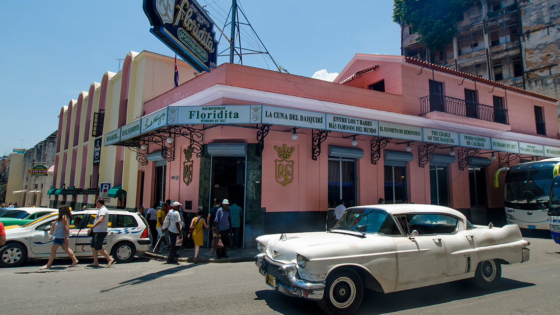 Vintage american from the 1950's tour the streets of Old Havana, in the background famous bar El Floridita