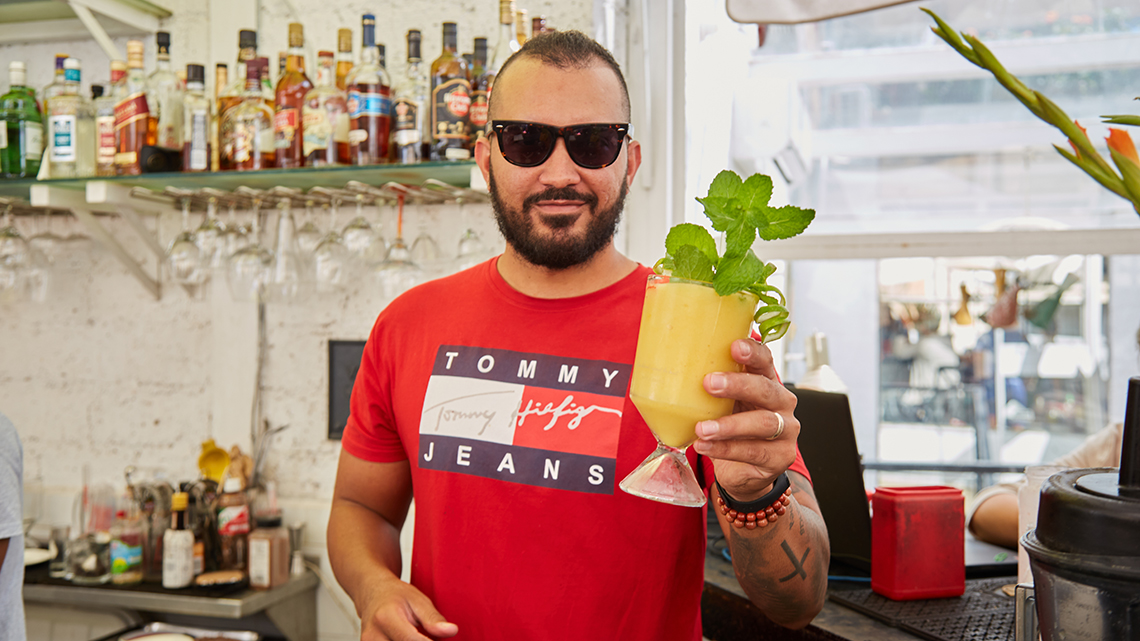 Bartender offering one of the cocktails that have made El del Frente famous in Havana