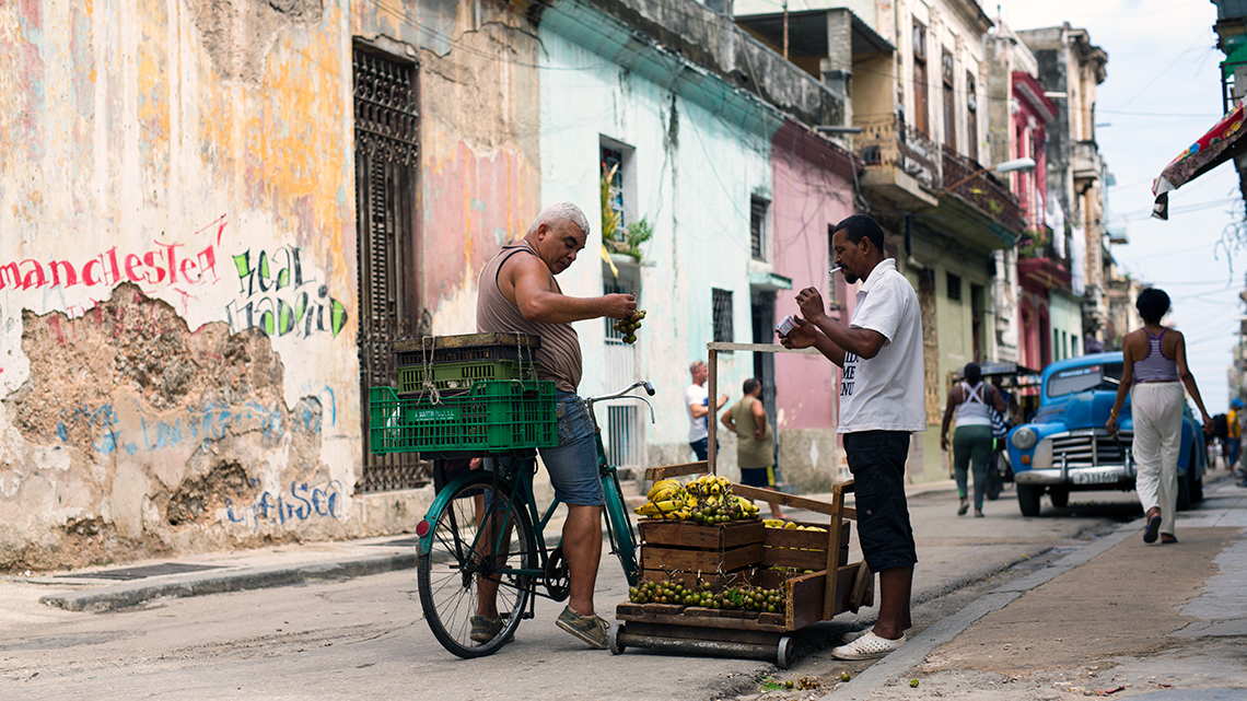 Habanero ask, from his bicycle, for fruit prices in the streets of Havana, Cuba