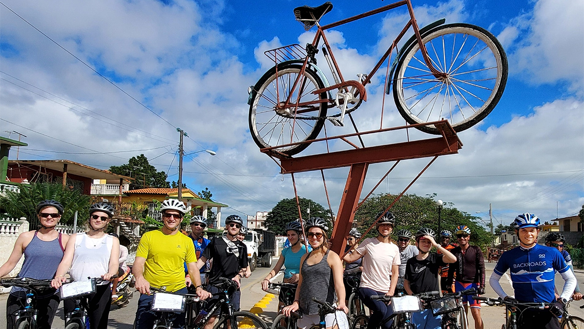 Tourist in a bicycle road tour visit Cardenas, Matanzas and take a photo in the monument to the bicycle in that city