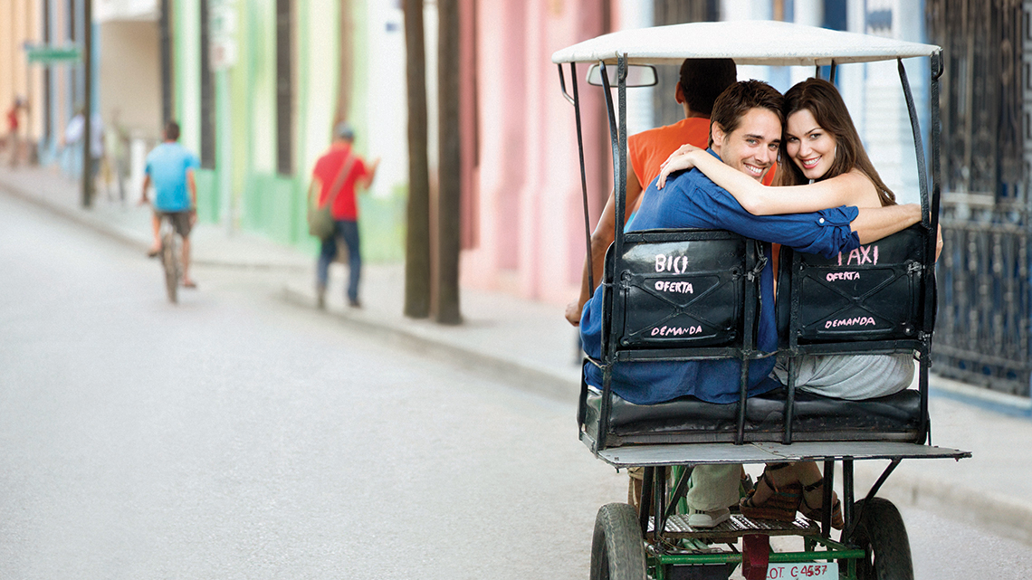 Romantic couple smilig to the camera from the back of a bicitaxi in the streets of Sagua la Grande, Villa Clara, Cuba