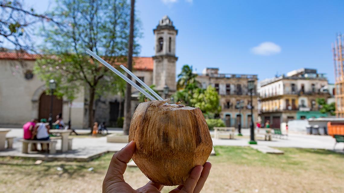 Tourist showing a coconut water drink, in the backgorund Cristo del Buen Camino church and the square of the same name
