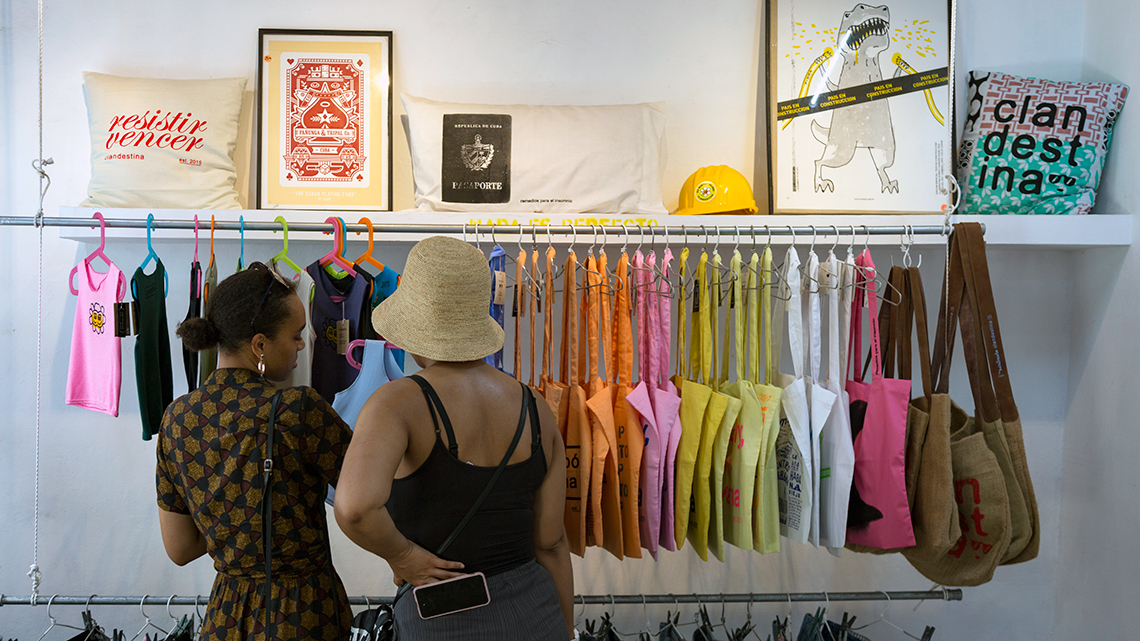 Tourist checking bags and t-shirts in 'Clandestina' a store located in Plaza del Cristo of Old Havana, Cuba