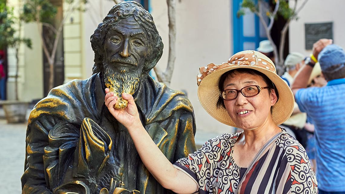 Tourist poses for photo holding the beard, for good luck, of El Caballero de Paris