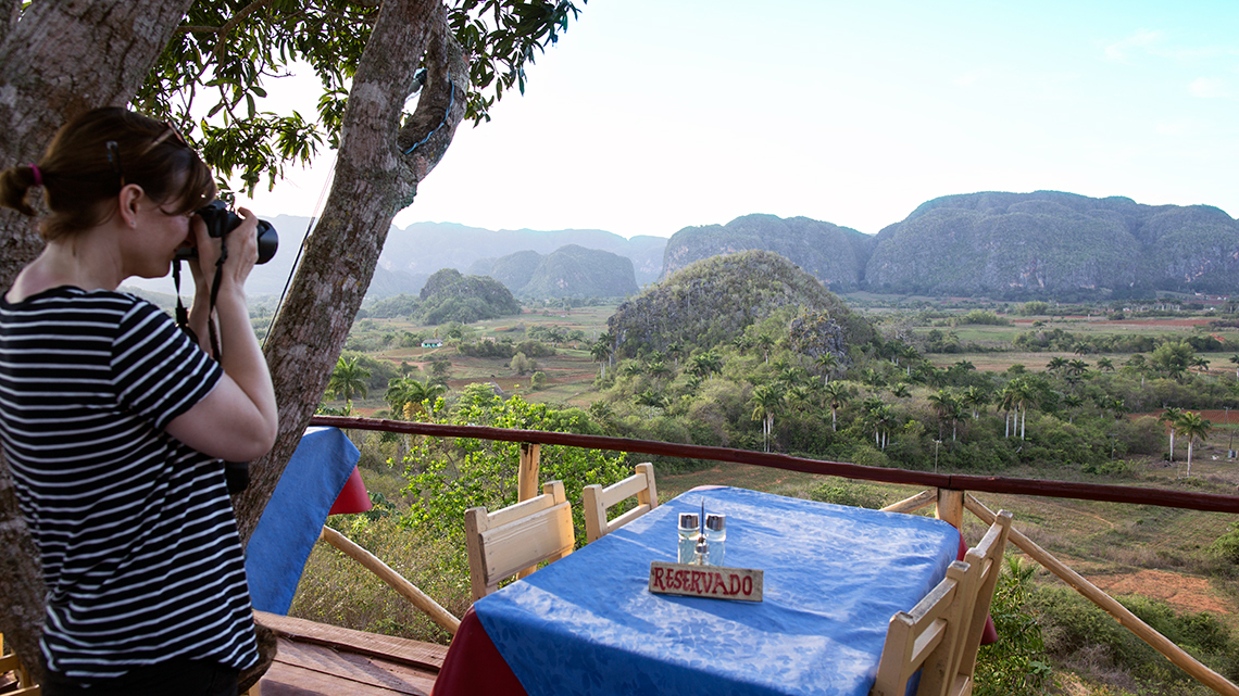 Traveller takes pictures of Vinales Valley from one of the local paladares