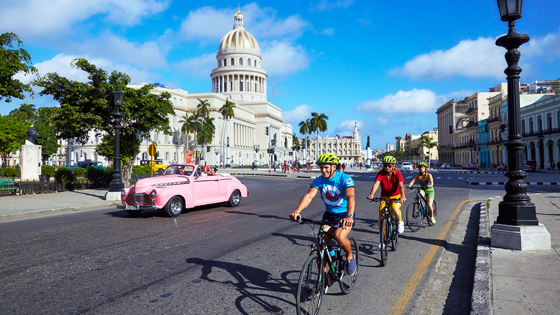 Cyclist pedaling the streets of Old Havana, in the backgorund the Capitol Building and a vintage American car from the 50s