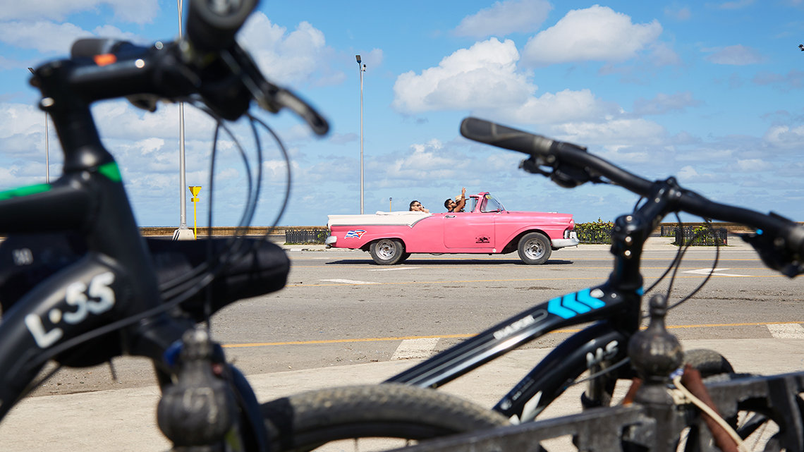 Vintage American car driving Havana's Malecon seeing through the handle bars of some bikes