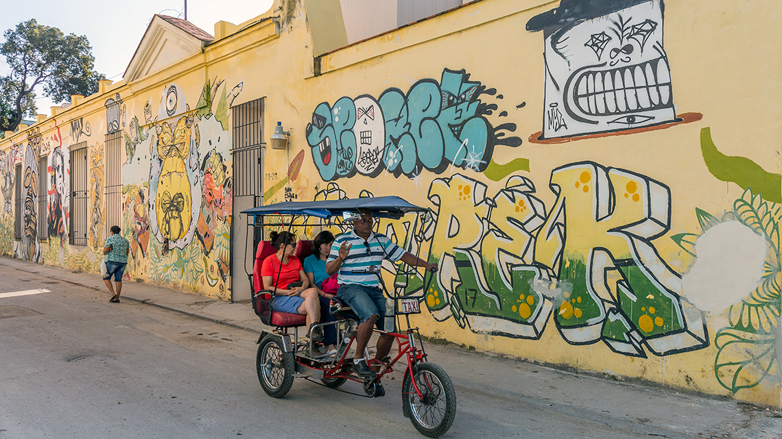 Bicitaxi riding along San Isidro in Old Havana, note the walls covered in graffiti from local artists