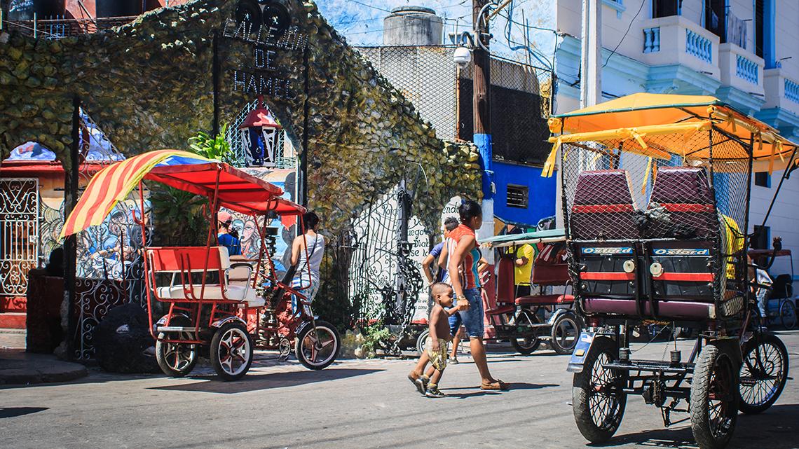 Bicitaxis parked outside the main entrance of Callejon de Hamel in Centro Habana