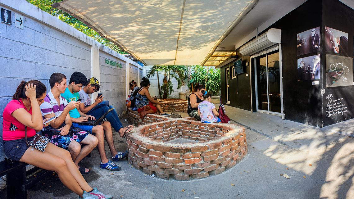 Local residents of Romerillo use the free internet at Kcho Estudio Romerillo