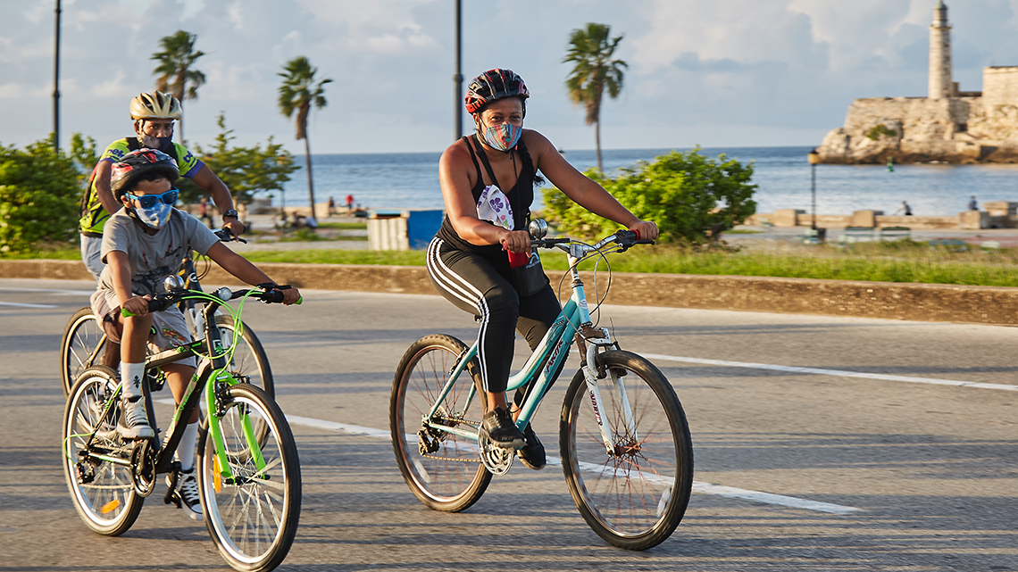 Mum and child riding in Critical Mass Havana, in the background Morro Castle Lighthouse