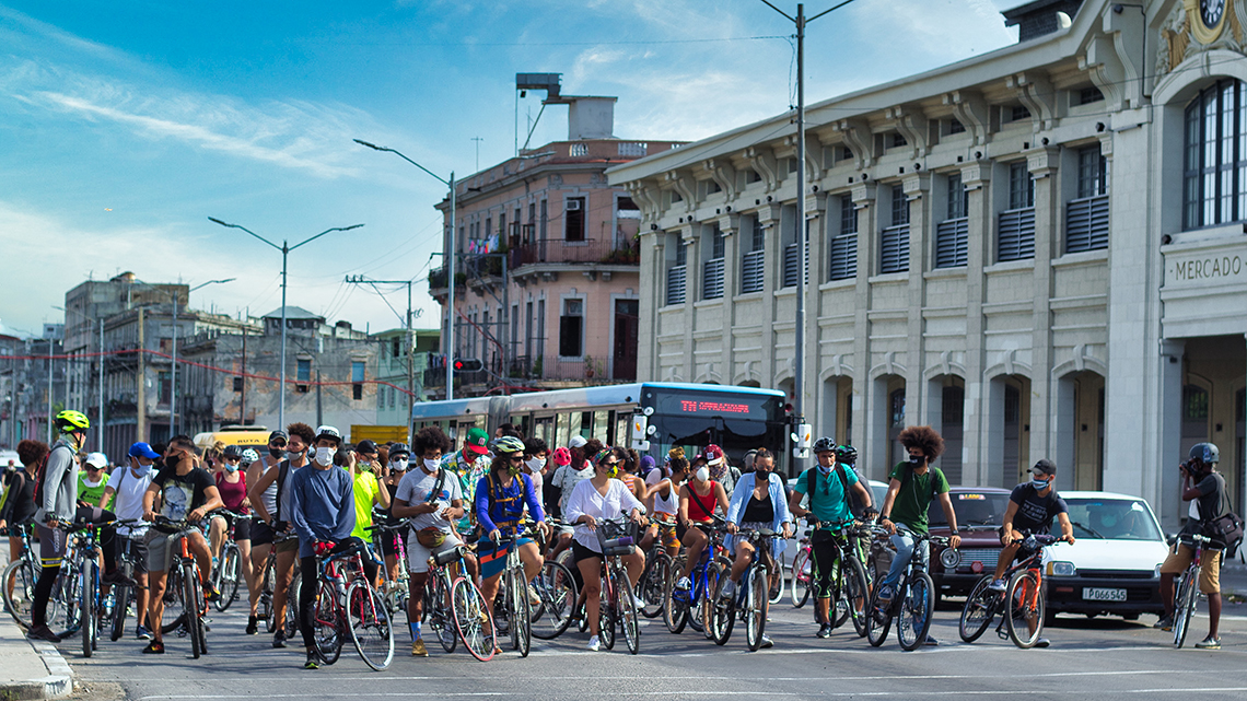 Platoon of bike riders waiting at a traffic light in Centro Habana