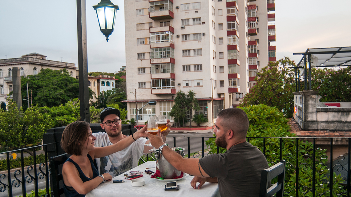 Friends enjoy drinks in the terrace of a house converted in paladar in Vedado