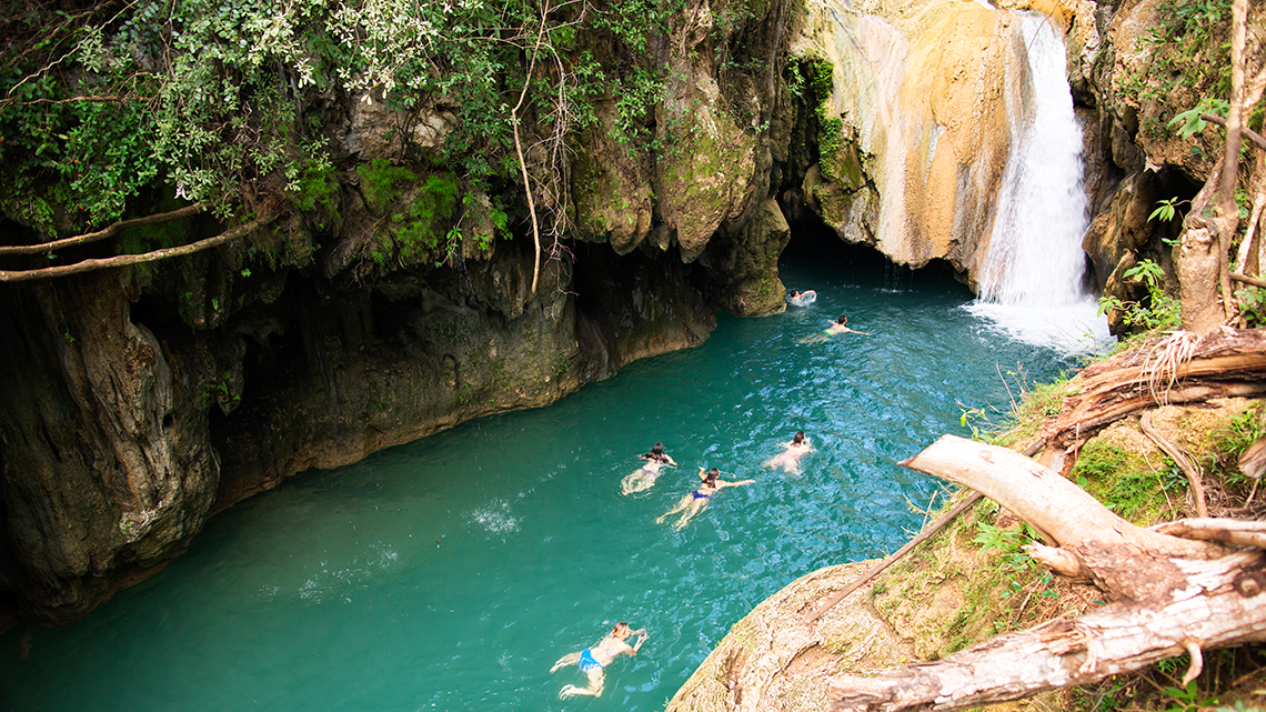 Holidaymakers swimming in one of the waterfalls of El Nicho in Cuba