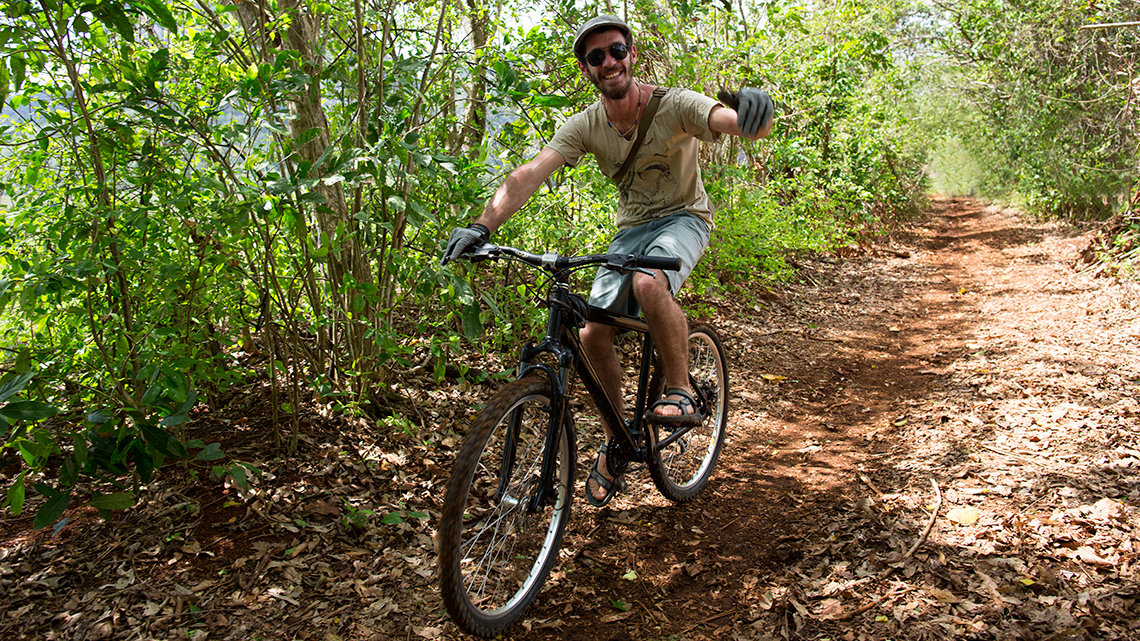 Tourist riding a bike in Vinales waves hello to the camera