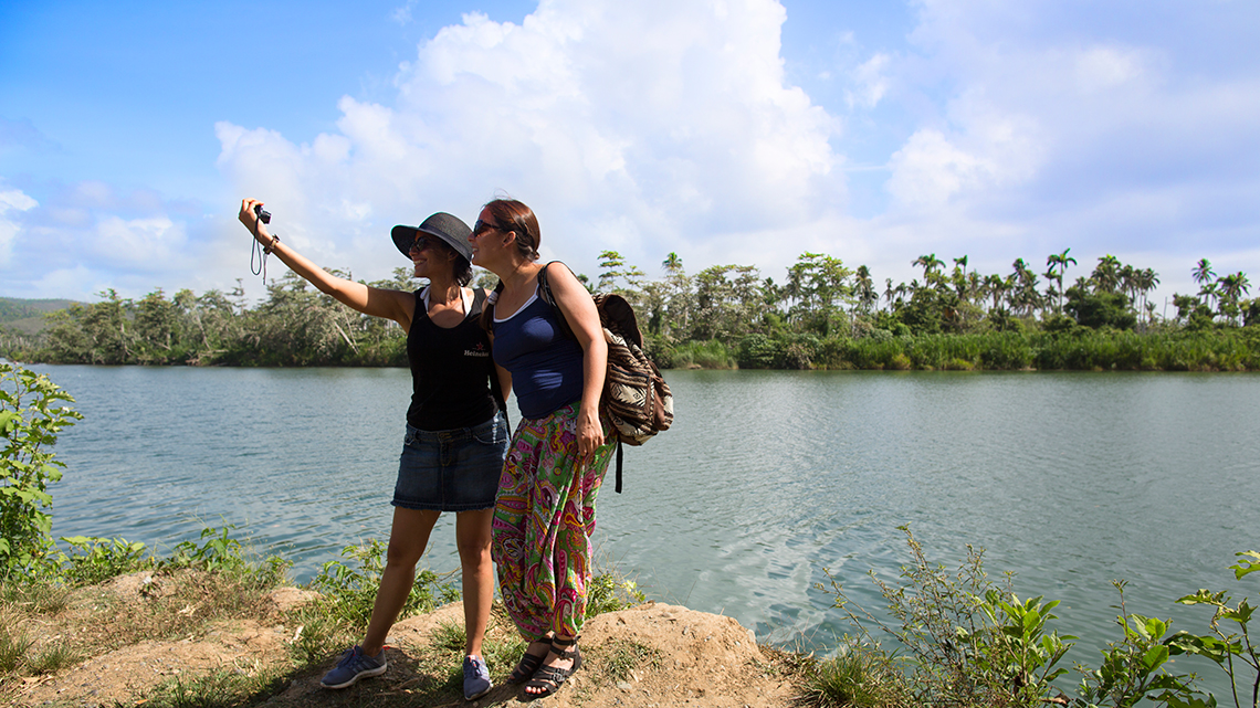 Travellers taking a selfie in banks of Toa river