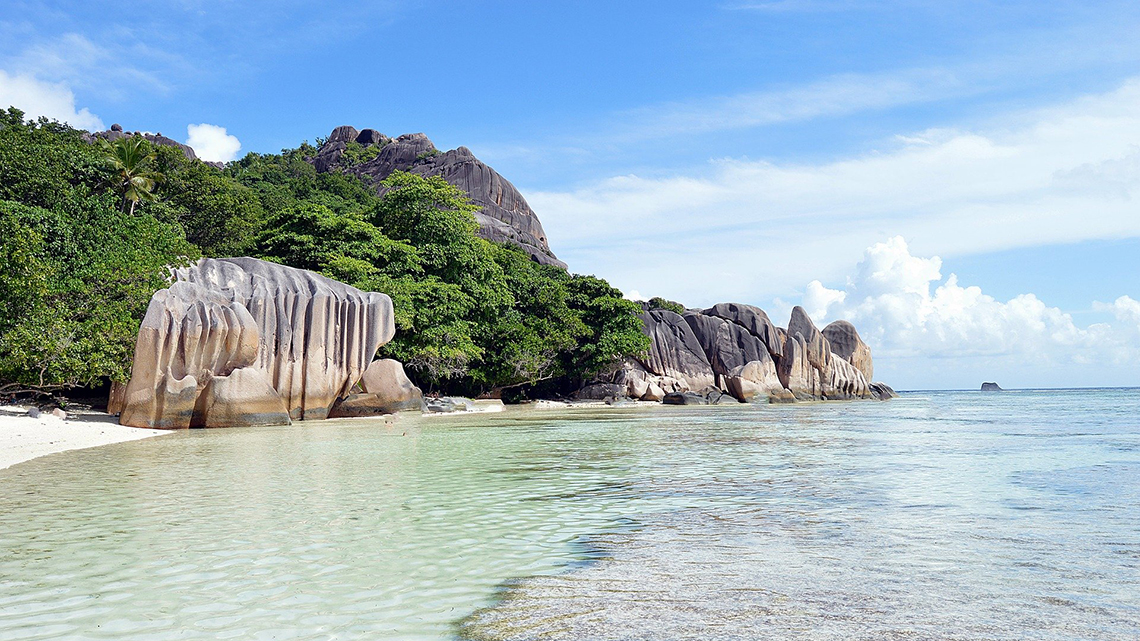 Massive rounded boulders on a white sand beach, one of the symbols of the Seychelles
