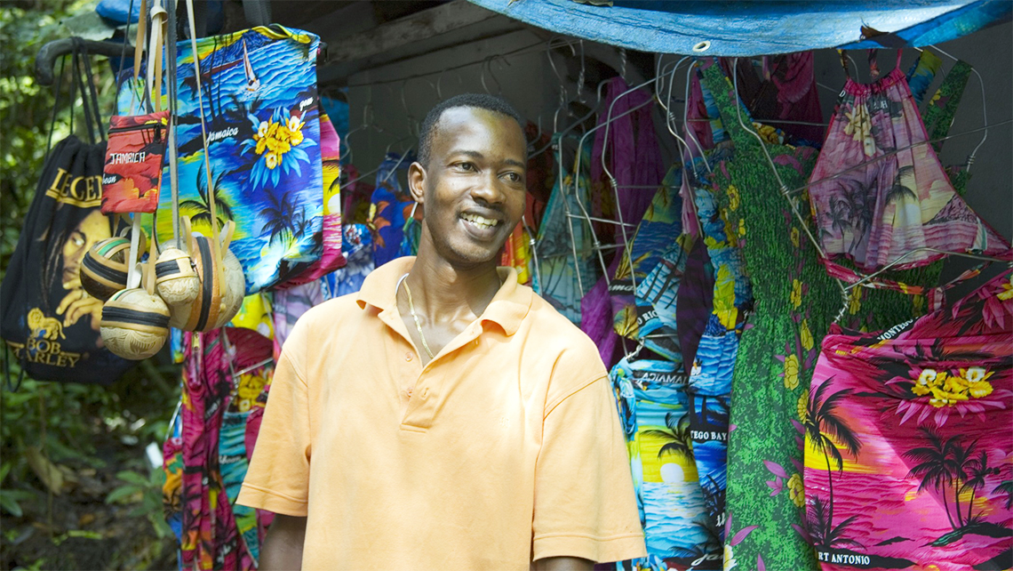 Young Jamaican man showing souvenirs to tourists