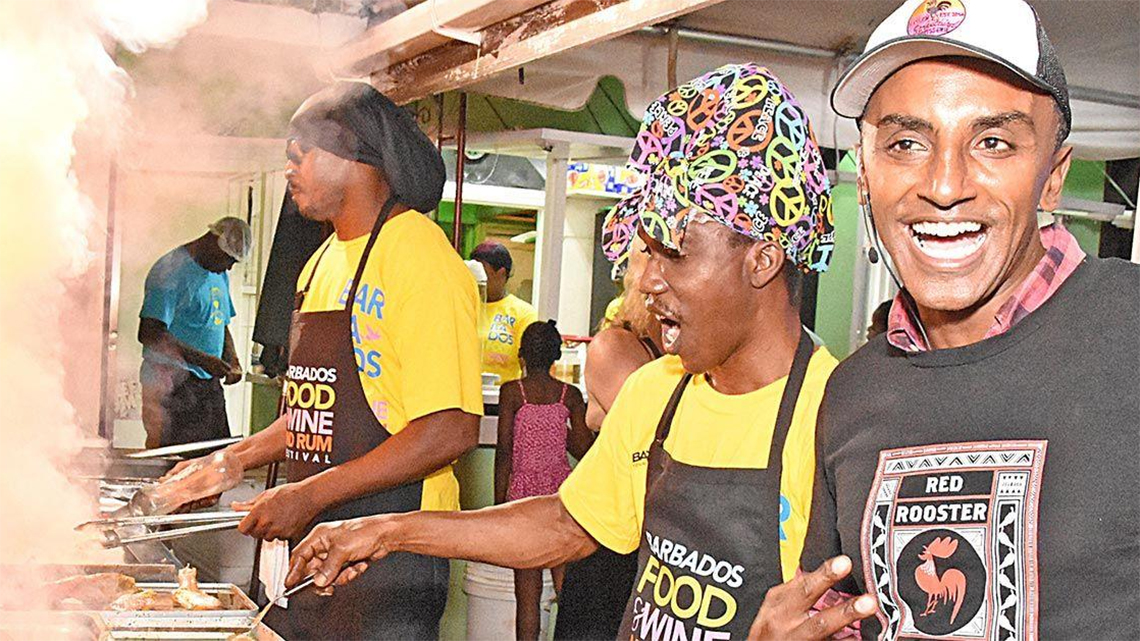 Chef in a street stall trading jokes with passing tourist in Barbados