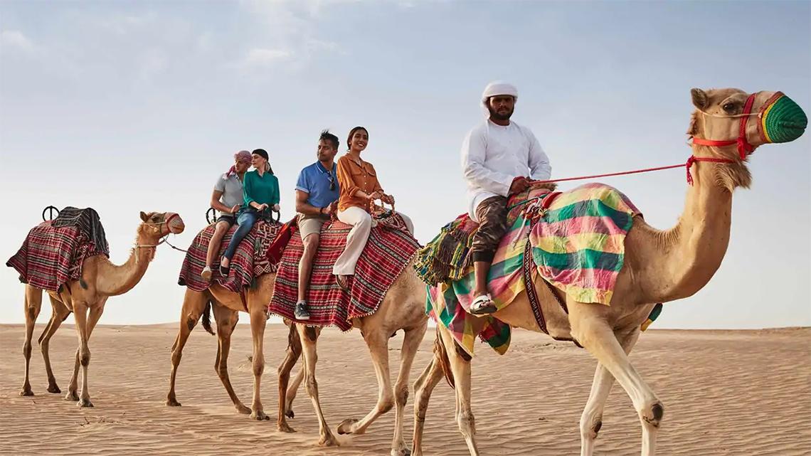 Tourists riding camels on a desert safari in Dubai